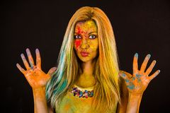 Beautiful young woman with colored powder. Over dark backgrond royalty free stock photography