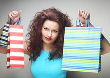 Beautiful young woman with colored shopping bags Royalty Free Stock Photos