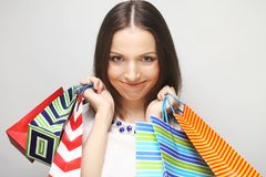 Beautiful young woman with colored shopping bags Stock Images