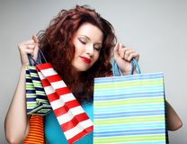 Beautiful young woman with colored shopping bags Royalty Free Stock Images