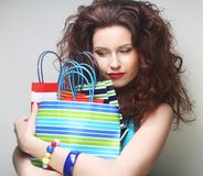 Beautiful young woman with colored shopping bags Stock Photos