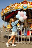 Beautiful young woman with balloons in the amusement park stock photo