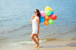 Beautiful young woman with colorful balloons over sea Royalty Free Stock Photography
