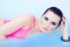 Beautiful young woman with colorful makeup in water Stock Photography