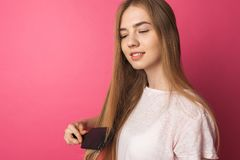 Beautiful young woman combing blonde long hair beauty and hairstyles, cute girl smiling stock photos