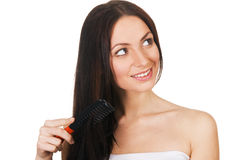 Beautiful young woman combing her hair Royalty Free Stock Photography