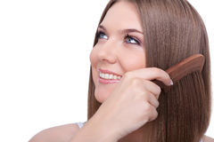 Beautiful young woman combing her hair Royalty Free Stock Images