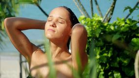 Beautiful young woman comes from the beach in outdoor shower. Sensual and seductive has a washing on summer holidays stock footage