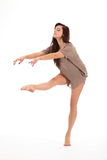 Beautiful young woman concentrates on dance moves. Beautiful young female dancer with one leg raised, toe pointed, demonstrating dance pose on white back ground Stock Image