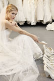 Beautiful young woman confused with footwear selection in bridal store Stock Photography
