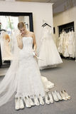 Beautiful young woman confused while selecting footwear in bridal boutique stock photo