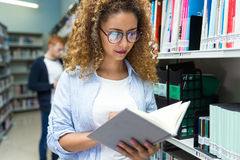 Beautiful young woman consulting a book in a university library. Portrait of beautiful young women consulting a book in a university library stock images