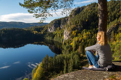 Beautiful young woman contemplating nature. On top of a cliff overlooking a beautiful lake stock image