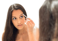 Beautiful young woman contouring her eyebrows stock photos