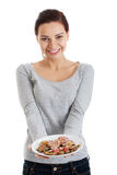 Beautiful young woman with cookies on a plate. Royalty Free Stock Photos
