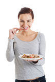 Beautiful young woman with cookies on a plate. Royalty Free Stock Image