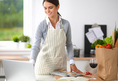 Beautiful young woman cooking looking at laptop Royalty Free Stock Photography
