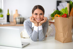 Beautiful young woman cooking looking at laptop Stock Images