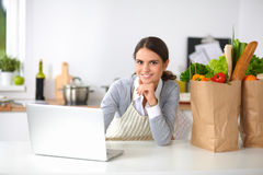Beautiful young woman cooking looking at laptop Stock Image