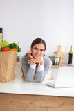 Beautiful young woman cooking looking at laptop Royalty Free Stock Image