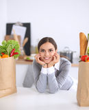 Beautiful young woman cooking looking at laptop Royalty Free Stock Images