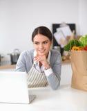 Beautiful young woman cooking looking at laptop Stock Photos