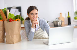 Beautiful young woman cooking looking at laptop Royalty Free Stock Photos