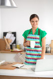 Beautiful young woman cooking looking at laptop Royalty Free Stock Photo
