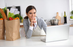 Beautiful young woman cooking looking at laptop Stock Photography