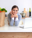 Beautiful young woman cooking looking at laptop screen with receipt in the kitchen Royalty Free Stock Image
