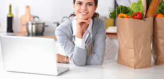 Beautiful young woman cooking looking at laptop screen with receipt in the kitchen Stock Images