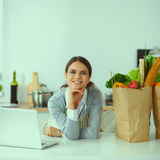 Beautiful young woman cooking looking at laptop screen with receipt in the kitchen Royalty Free Stock Images