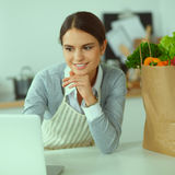 Beautiful young woman cooking looking at laptop screen with receipt in the kitchen Stock Photo