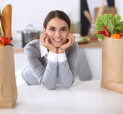 Beautiful young woman cooking looking at laptop screen with receipt in the kitchen Stock Image