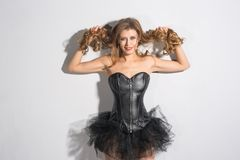 Beautiful young woman in a corset and a skirt. On a gray background royalty free stock photos