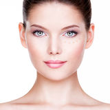 Beautiful young woman with cosmetic foundation on a skin. Stock Photography