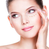 Beautiful young woman with cosmetic foundation on a skin. Stock Image