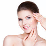 Beautiful young woman with cosmetic foundation on a skin. Royalty Free Stock Images