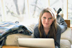 Beautiful young woman on couch in pajamas with laptop Royalty Free Stock Images