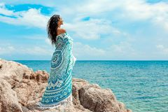 Beautiful young woman covered with blanket on the beach Royalty Free Stock Photos