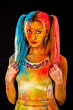 Beautiful young woman covered with colored powder Stock Image