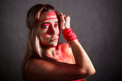 Beautiful young woman covered with red paints Royalty Free Stock Photos