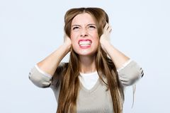 Beautiful young woman covering her ears over gray background. Royalty Free Stock Image