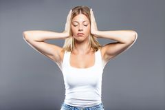 Beautiful young woman covering her ears over gray background. Royalty Free Stock Images