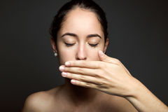 Beautiful young woman covering her mouth with hand. Isolated. Portrait of beautiful young woman covering her mouth with hand. Isolated Royalty Free Stock Photography