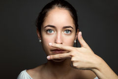 Beautiful young woman covering her mouth with hand. Isolated. Royalty Free Stock Photography