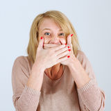Beautiful young woman covering her mouth by the hands while Royalty Free Stock Photos