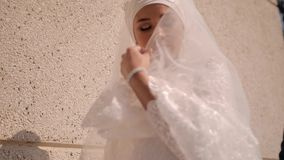 A beautiful young woman covers her face with her snow-white dress and opens her face again stock video footage