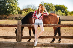 Beautiful young woman cowgirl staning with her horse on ranch Stock Image