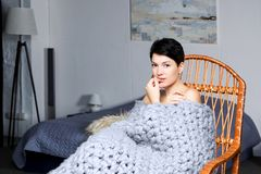 Beautiful young woman in cozy plaid in armchair. Beautiful young woman with a short haircut sits in the bedroom in a wicker chair, wrapped in a woolen knitted Royalty Free Stock Images